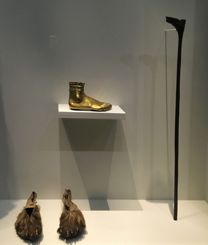 Fig. 1. Left to right: Bearskin moccasins, mid-Mississippi region, United States, eighteenth century, bear-skin, tendons, claws, Musée du quai Branly, Paris; Foot reliquary of Saint Adalard, Italy, sixteenth century, stamped, engraved, chased, and gilded copper, 12.4 x 20.8 cm, Musée national du Moyen Âge – Thermes de Cluny, Paris; Zulu shoe-cane, South Africa, ca. 1910, wood 91.5 x 8.6 x 2.5 cm, Musée du quai Branly, Paris. Installation view, Carambolages, Grand Palais, Paris. Photo © the author.